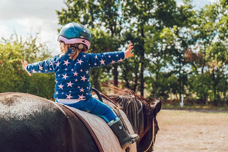 Ein kleines Kind auf einem Pferd ohne Steigbügel.