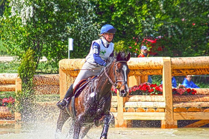 Vielseitigkeitsreiterin mit ihrem Pferd beim Wasserdurchritt.